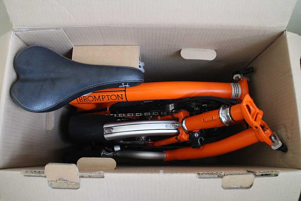 Das Brompton Faltrad kompakt verpackt: Mit Reisemaß im Karton verpackt