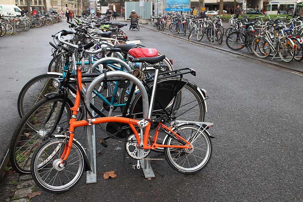 Große Fahrrad-Parkplätze sind nicht so sein Ding. Diebstahlsicher ist das Mitnehm-Faltrad nur mit sehr gutem Schloss. Ansonsten: Mitnehmen.